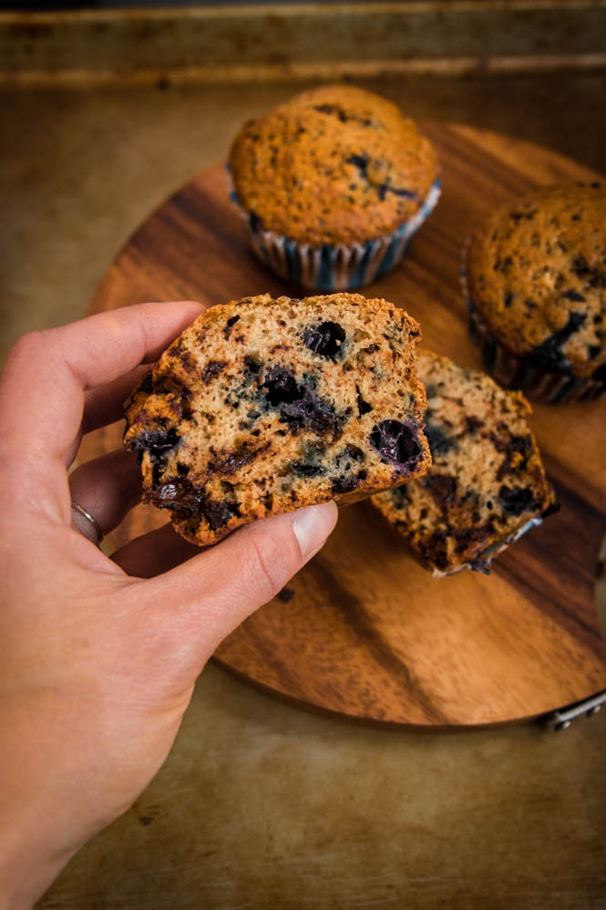 hand holding a muffin, wooden board