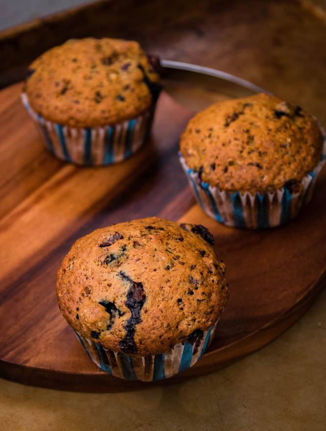 three blueberry chocolate muffins on a wood board
