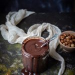 jar of homemade Nutella, cheesecloth, hazelnuts in a bowl