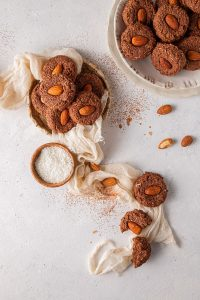 cookies on a plate with cheesecloth, small bowl of shredded coconut and almonds laying on a table
