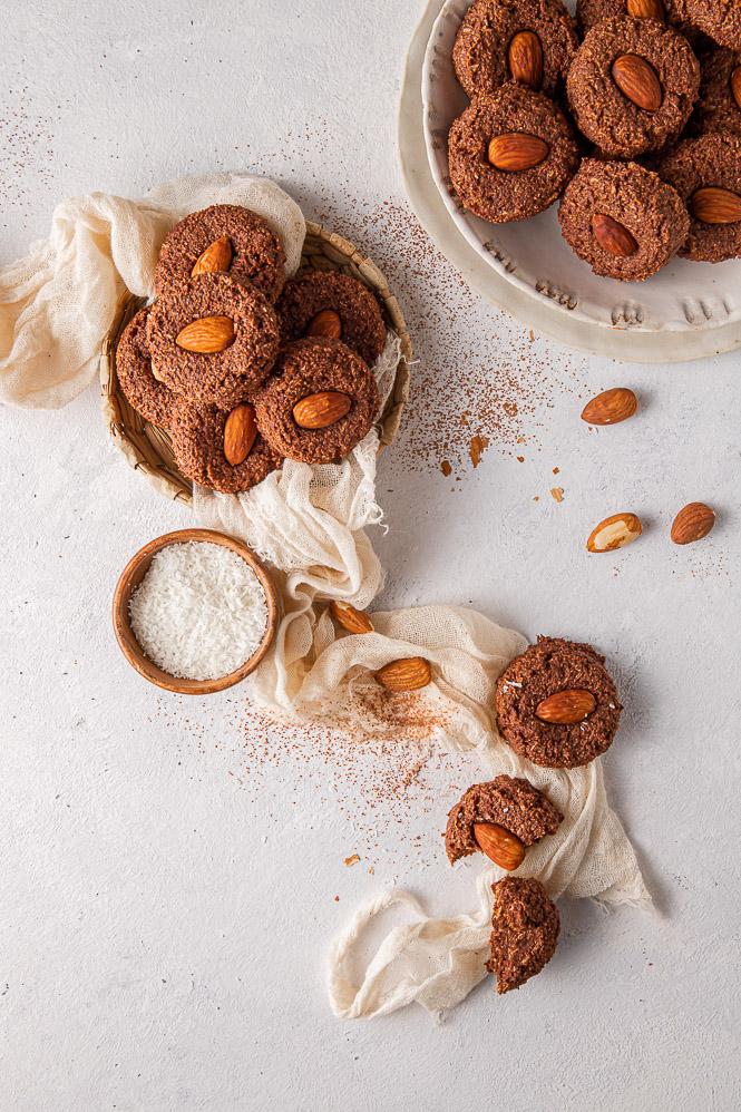 Cookies in a bow with cheesecloth, small bowl with shredded coconut, sprinkled almonds and cacao powder on the table