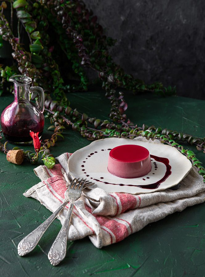 Hibiscus panna cotta on a plate with a napkin underneath. Two forks, glass jar and a plant