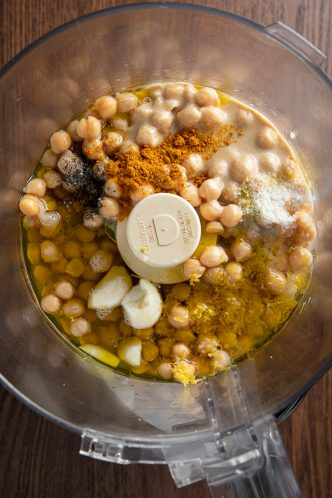 Food processor with chickpeas, tahini, black pepper, turmeric powder, garlic cloves, lemon zest, salt.