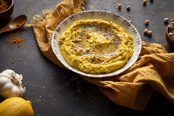 Bowl with turmeric hummus, yellow napkin under the bowl, garlic head to the side and a lemon, wooden bowl with turmeric powder and a wooden spoon on the side, turmeric powder sprinkled of the spoon, bowl with garbanzo beans and some on the table.