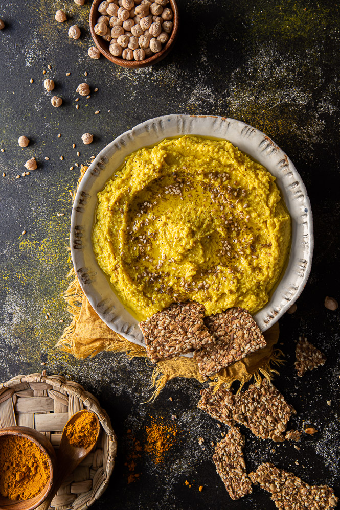Bowl with turmeric hummus and crackers in the bowl and on the table, yellow napkin under the bowl, small wooden bowl with garbanzo beans and some scattered on the table, small wooden bowl with turmeric powder and a wooden spoon on the side with turmeric on and off the spoon.