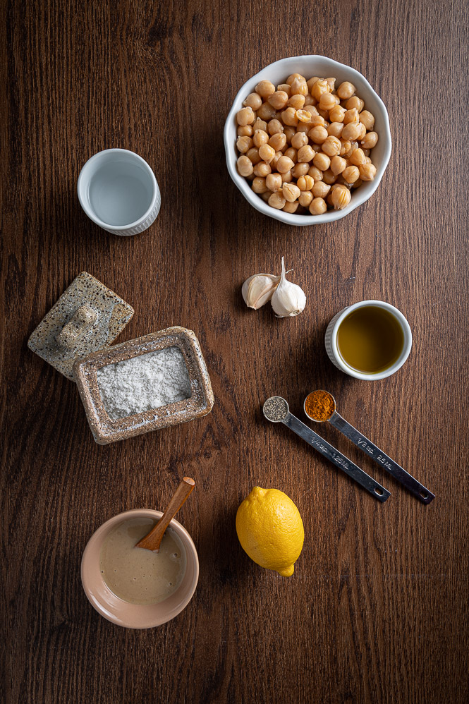 Bowl with chickpeas, two garlic cloves, ramekin with olive oil, ramekin with water, salt in a jar with a lid on the side, measuring spoon with black pepper, measuring spoon with turmeric, lemon, little bowl with tahini and a wooden spoon.