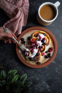 A plate with three pancakes topped with yogurt and berries. Cup of coffee on the side and a napkin next to the plate. A hand holding a fork and reaching for a pancake.