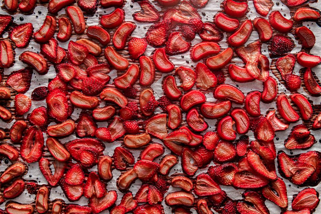 Roasted chopped rhubarb and strawberries spread on a parchment paper and drizzled balsamic reduction.