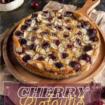 Cherry Clafoutis on a round wooden board, lying on top of a brown paper. Cherries scattered around with a bowl of fresh cherries on the side. White plate with two forks in far corner.
