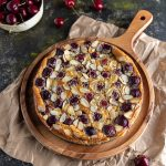 Cherry Clafoutis on a round wooden board, lying on top of a brown paper. Fresh cherries scattered around. And a bowl or fresh cherries on the side.