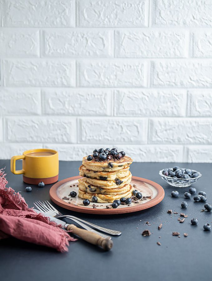 Stack of pancakes on a plate topped with shaved chocolate and fresh blueberries. Yellow cup of coffee on the left side, small glass bowl full with fresh blueberries on the right side with blueberries and chocolate scattered on the table. Fork and knife by the side of the plate with a pink napkin next to them.
