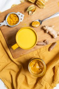 Yellow cup with golden latte in it, sitting on a wooden cutting board. Pieces of turmeric and ginger on the side. Tea spoon with golden honey next to the cup. golden berries at the corner and a sieve with graded ginger and turmeric on the left to the cup. Ywllow hapkin under the cutting board with a glass jar filled with golden honey.