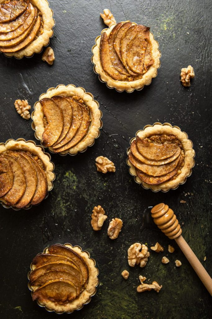Six Apple Walnut Tartlets scattered around with pieces of fresh walnuts all around. Wooden honey dipper on the bottom right corner.