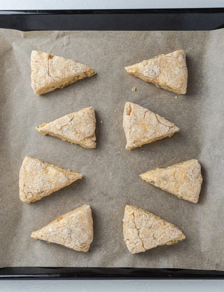 Raw scone slices on a parchment paper in a baking tray.