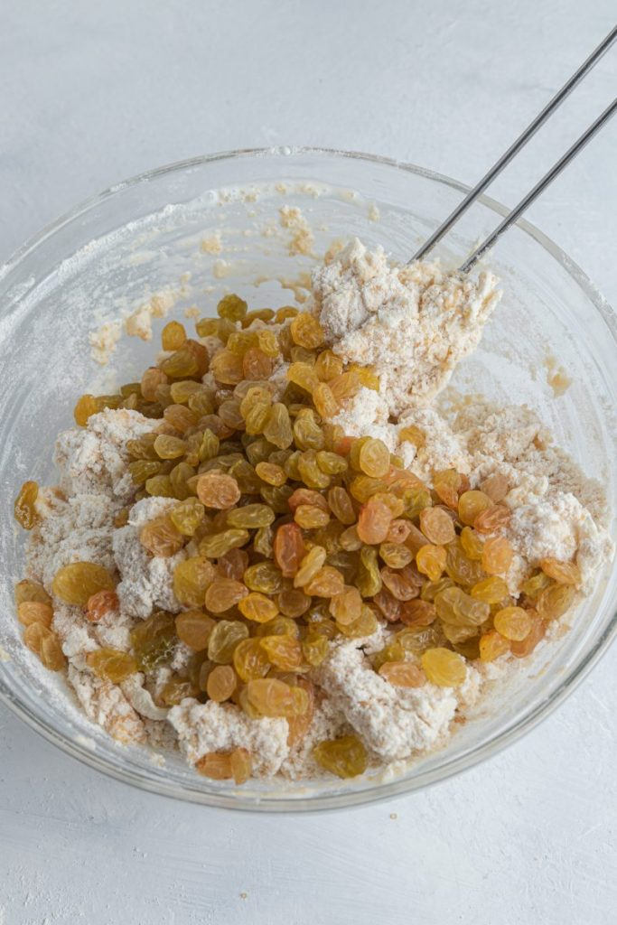 A glass bowl filled with batter mix and golden raisins on top, about to be mixed into the batter.