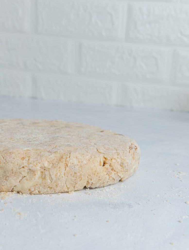 Round disk shaped side view of a raw scone dough.
