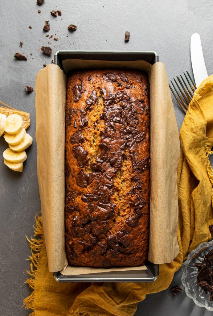 A rectangular baking tray lined with parchment paper and filled with freshly baked Chocolate banana bread. Yellow napkin underneath. Two forks and a knife sticking of the napkin on the right. Little glass plate with pieces of chocolate in the right bottom corner. Chocolate pieces scattered on the table next to the baking tray. And a pick of a chopped banana pieces on the left side.