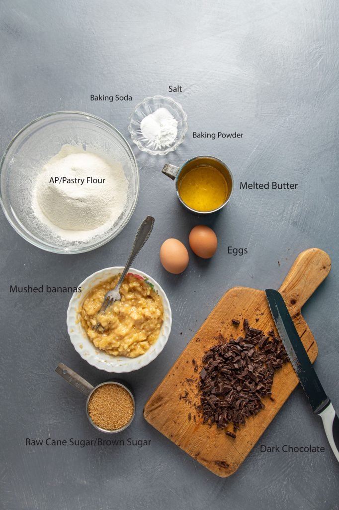 Ingredients for Chocolate Banana Bread recipe. A large glass bowl with flour. A small ramekin with baking powder, baking soda and salt. A cup with melted butter. Two eggs. A bowl with mushed bananas. Measuring cup with raw cane sugar or brown sugar. Wooden cutting board with chopped chocolate and a serrated knife leaning on the board.