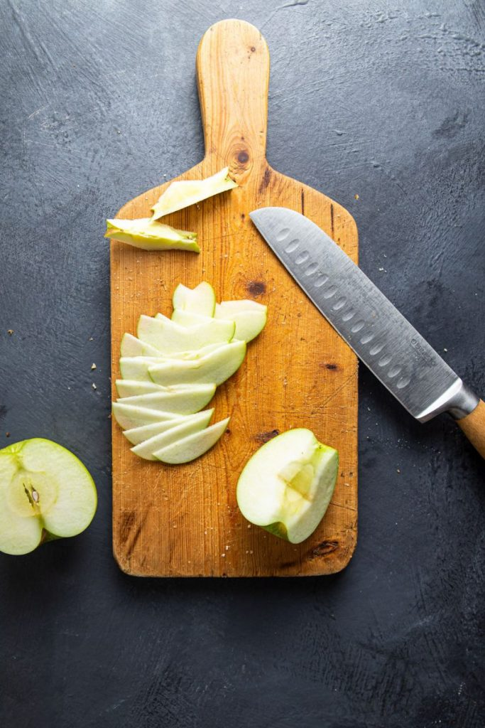 Apple slices on a cutting board with a knife leaning on the side. Half apple on the left side of the board.