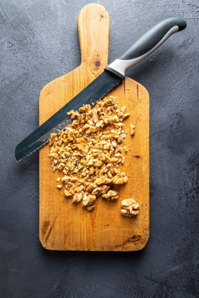 Chopped walnuts on a wooden board with a knife next to them.
