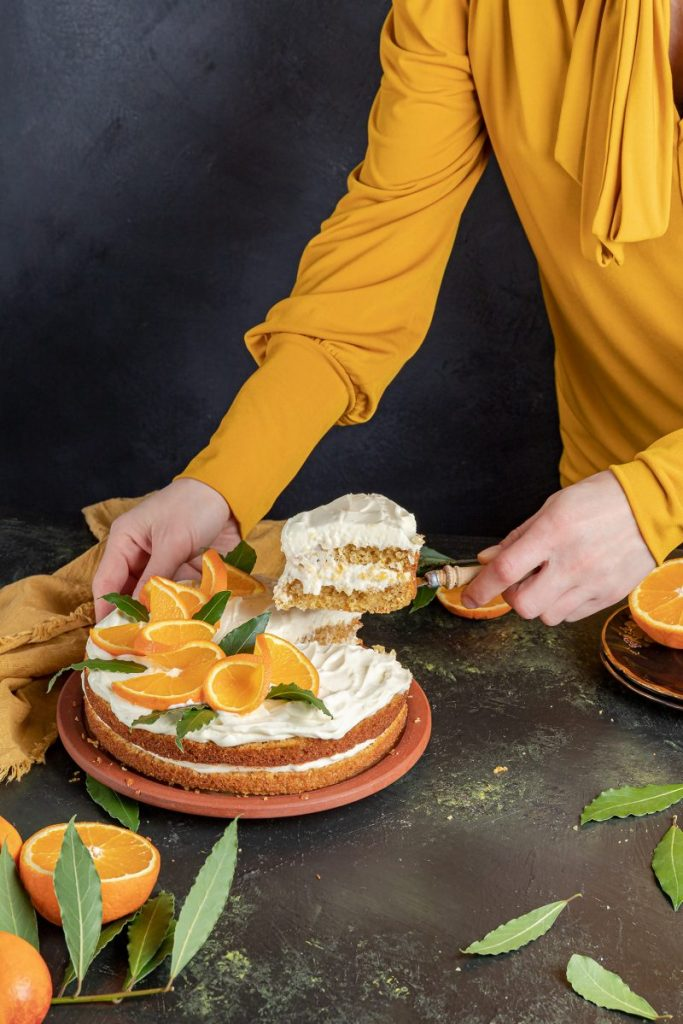 Female from the chest down wearing a yellow shirt holding a cake with one hand and lifting a slice of the cake with the other hand. Napkin laying on the left side and two stacked up plates on the right side with a sliced in half orange on top. Few oranges on the near left side with orange leaves around it.