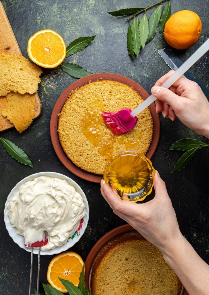 Cake at the center with two hands, one holding a glass ramekin filled with orange syrup and the other hand spreading the syrup on the bottom layer of the cake using a silicon brush. The cake is surrounded by whole and half oranges, green leaves. A bowl of mascarpone cream cheese on the right side next to the cake with a spatula in it. Bread knife picking on the right. Another plate with the other half of the cake in the lower left corner. Wooden cutting board with pieces of the cake picking out on the upper left corner.