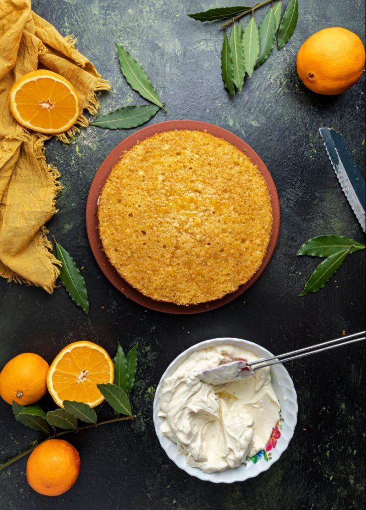 Cake at the center surrounded by whole and half oranges, green leaves and a yellow napkin at the upper left corner. A bowl of mascarpone cream cheese with a spatula in it. Bread knife picking on the right.