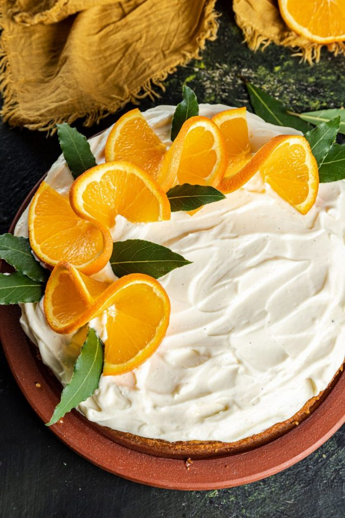 Orange Layer Cake with Mascarpone Cream Cheese Frosting on a plate. Yellow napkin on the upper corner with a pick of a half orange.