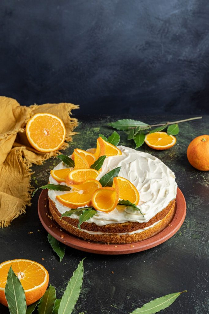 Orange Layer Cake with Mascarpone Cream Cheese Frosting on a plate. Yellow napkin on the left side with a half of an orange on it. Another orange half on the near left side with green leaves picking out. Orange on the far right side and an orange wheel, green leaves around it.