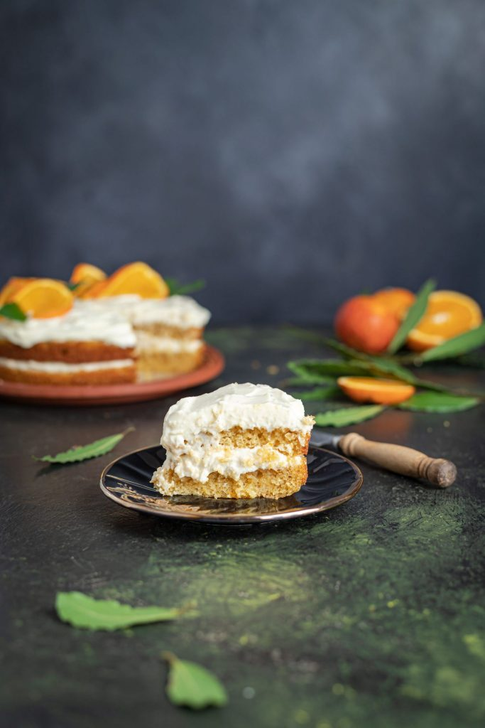 Slice of Orange Layer Cake with Mascarpone Cream Cheese Frosting on a black plate. Wooden knife handle visible next to the plate. On the far left is the cake and far right oranges with one cut out. Orange leaves scattered around the table.