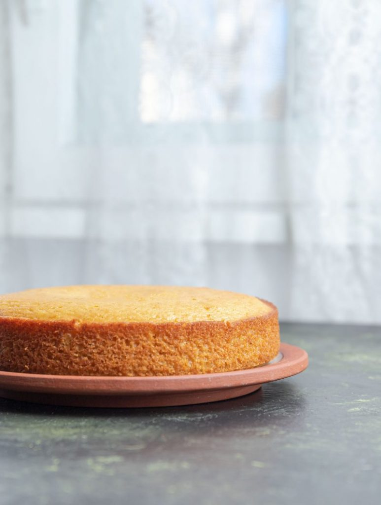 Cake on a plate from a side view. Window with a lace curtain in the background.