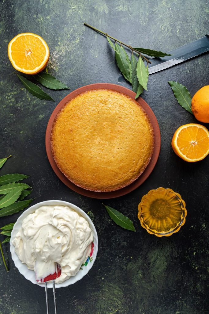 Cake on a plate at the center. Surrounded by half oranges and green leaves. A white bowl with frosting and a spatula at the lower left corner. Bread knife at the upper right corner. A small glass ramekin with orange syrup.