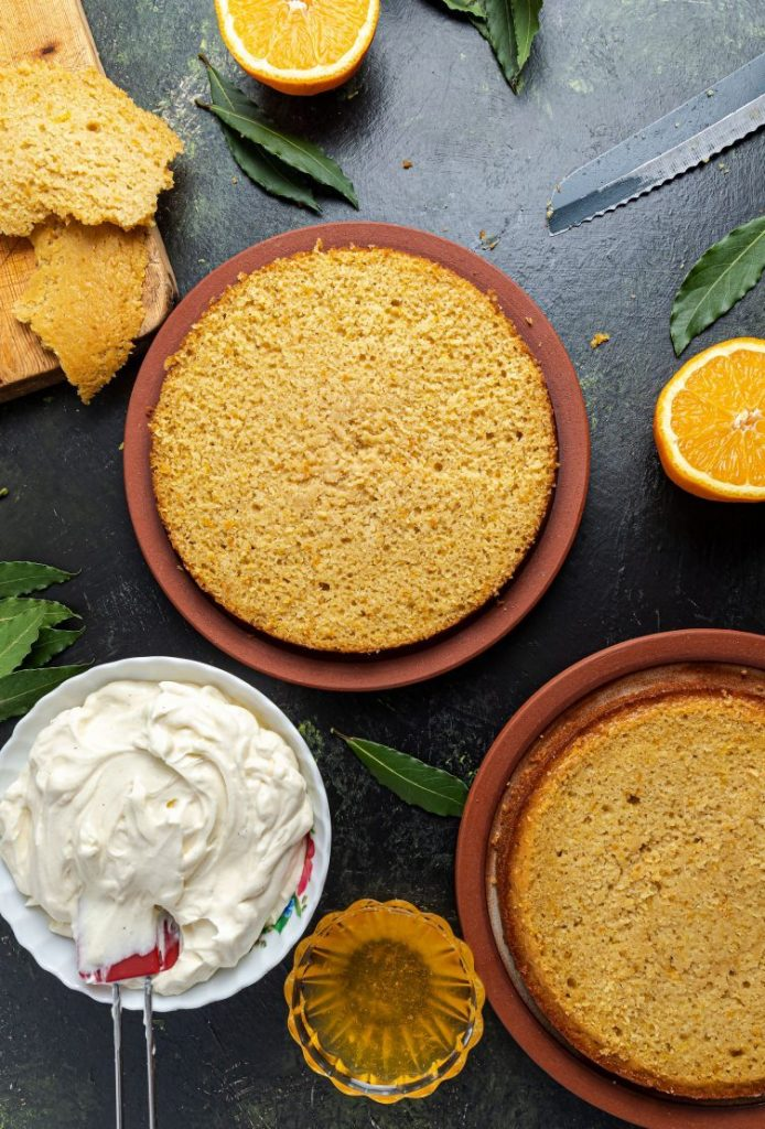 Two layers of cake on two plates next to each other. One bowl with frosting and spatula. Small glass ramekin with orange syrup between the cake and frosting. Two half oranges, one on the upper corner and one on the right side. Green leaves scattered all around. Bread knife picking out on the upper right corner. Wooden cutting board with thin slices of the cake on the upper left corner.