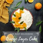 Orange Layer Cake with Mascarpone Cream Cheese Frosting at the center surrounded by whole and half oranges, green leaves and a yellow napkin at the upper left corner.
