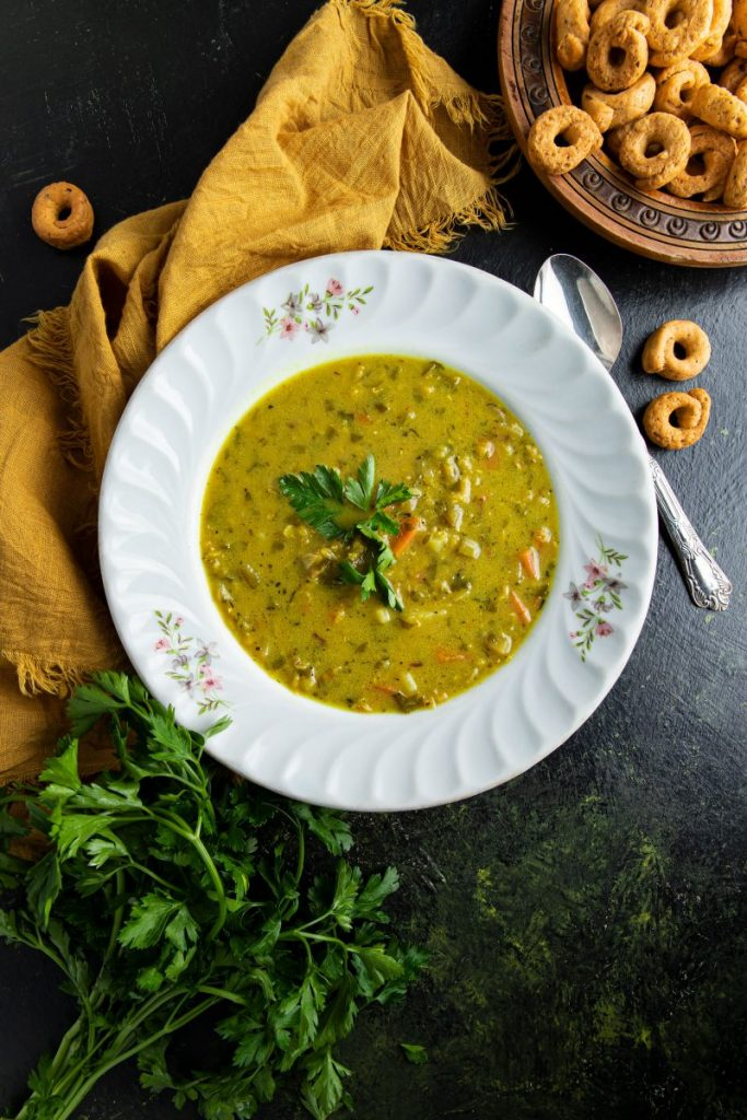 Split Pea Soup in a bowl surrounded by a yellow napkin, a spoon and a bunch of parsley at the bottom left corner. At the top right corner a engraved wooden plate with crispy round pretzels.