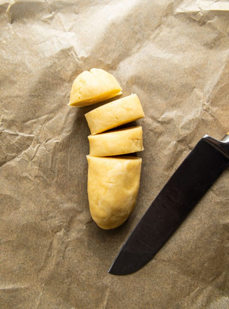 Sliced dough and a knife next to it, on top of a parchment paper.