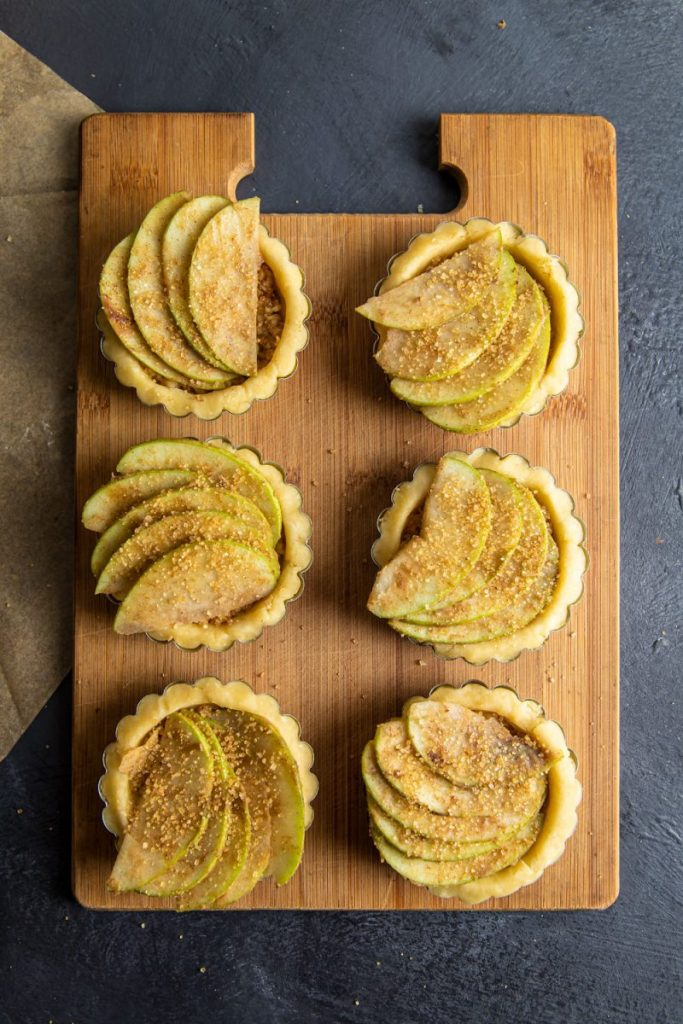 Six Apple Walnut Tartlets laying on a wooden cutting board ready to bake.