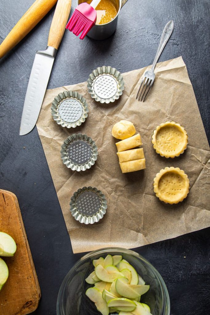 Six tartlet forms, two of them already have the dough pre-shaped in them. Sliced dough in the center of the forms, all laying on a parchment paper. One fork on top right side. On the left top side there is a knife a cup with melted butter and a brush on top, rolling pin next to the knife. On the bottom right side a glass bowl with sliced apples in it. Wooden cutting board partially visible on the left side with apple pieces on it.