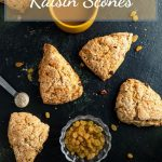 Six scones laying on a dark green surface with a yellow cup in between filled with coffee. A small glass bowl in the bottom part between the scones filled with golden raisins. Measuring spoon on the left side with cardamom powder in it. And golden raisins scattered around the table.
