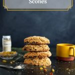 Four scones stacked one on top of each other. Yellow cup on the right side. Small glass bowl with golden raisins in it and some scattered around. Glass container, behind the glass bowl, filled with cardamom powder. Measuring spoon in the foreground with cardamom powder.