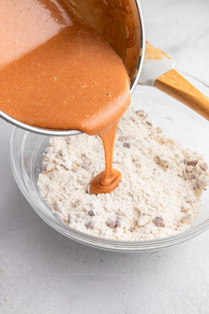 Dulce de leche egg mixture being poured into a glass bowl filled with flour, coconut and chopped almonds.