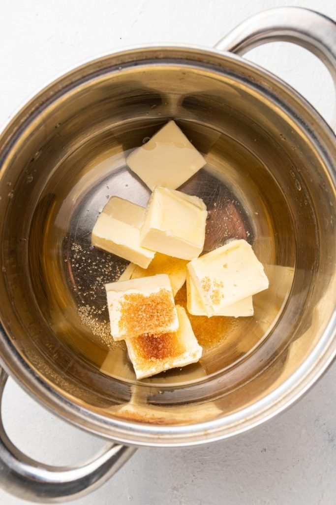 A saucepan with water, butter cubes, and brown sugar in it.