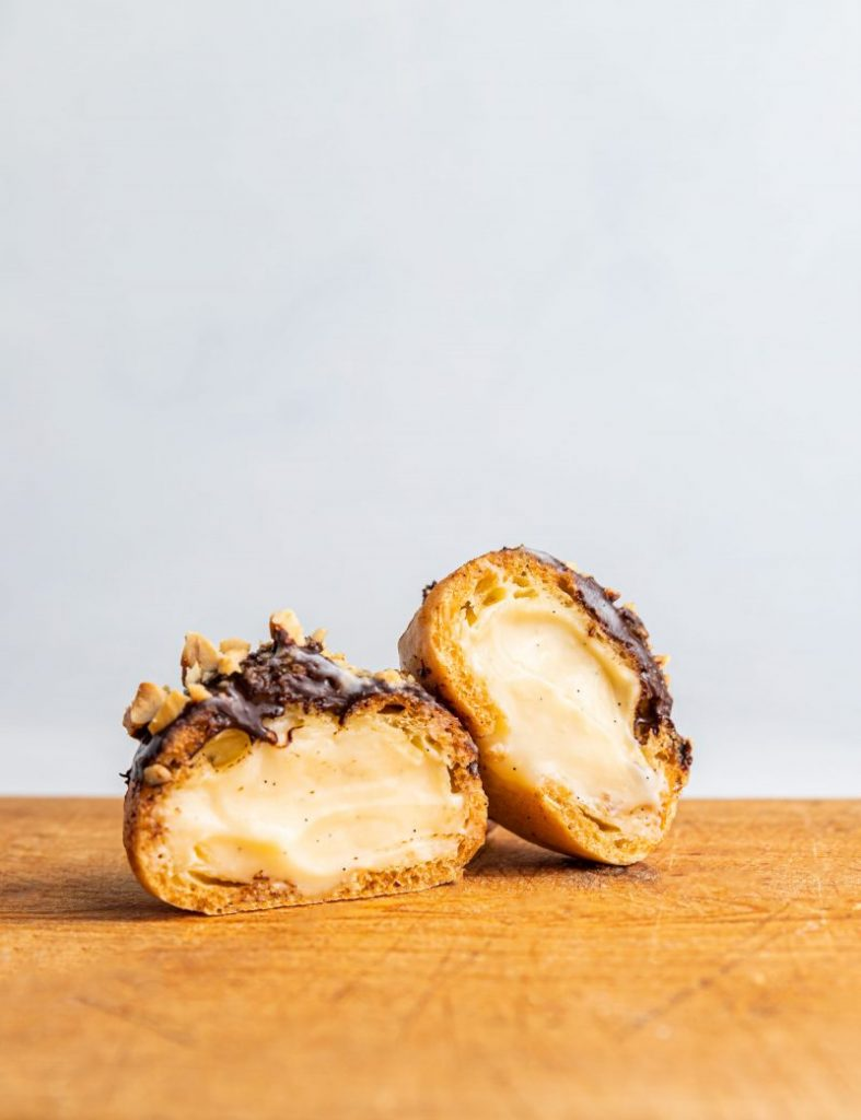 Profiterol cut in half showing the filling. Its tipped with chocolate and nuts. One half is leaning on the other half. White background and a wooden surface.