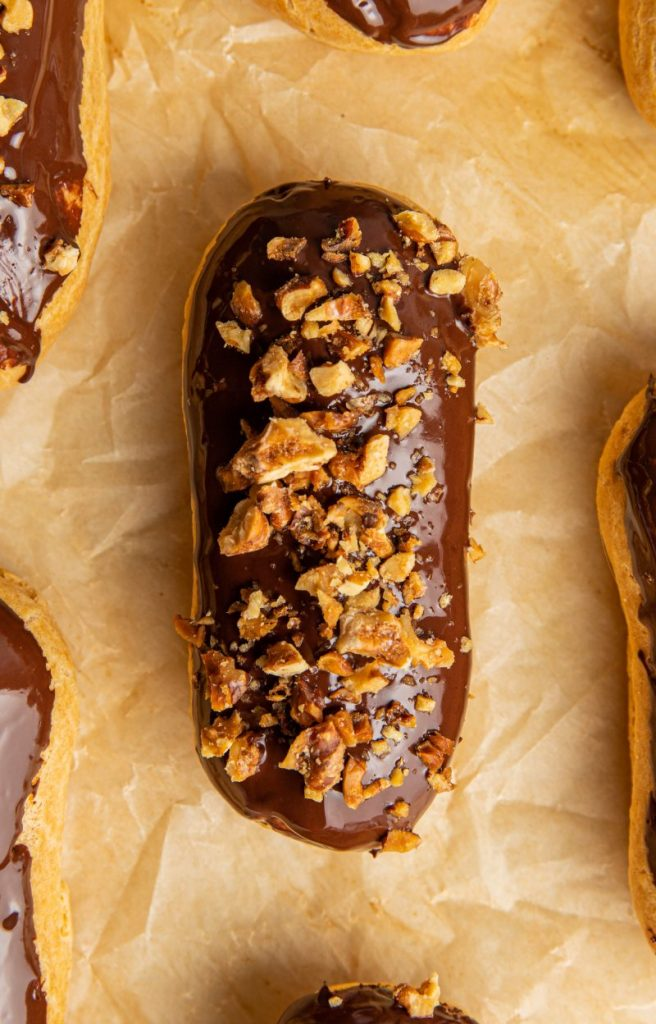 Eclair dipped in chocolate and covered with chopped nuts. Surrounded by other eclairs and laying on a parchment paper.