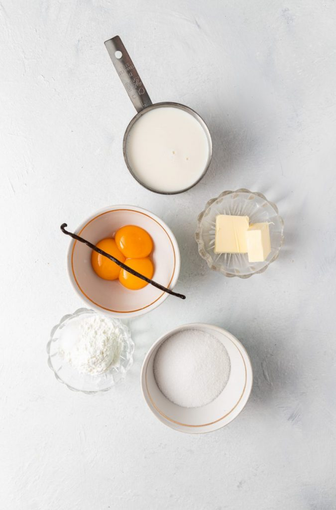 Measuring cup with milk, small glass ramekin with two cubes of butter, small bowl with sugar, small glass ramekin with corn starch, and a bowl with three egg yolks and a vanilla bean on top.