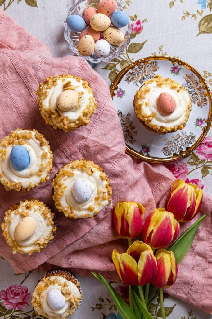 Cupcakes with white frosting, nuts and candies eggs on top. Some of the cupcakes are sitting on a pink napkin. One cupcake is on a pircelain plate with a gold trim and detailed decoration. Red and yellow tulips placed next to the cupcakes on the bottom right side. Small glass bowl with colorful candies eggs on the upper side.
