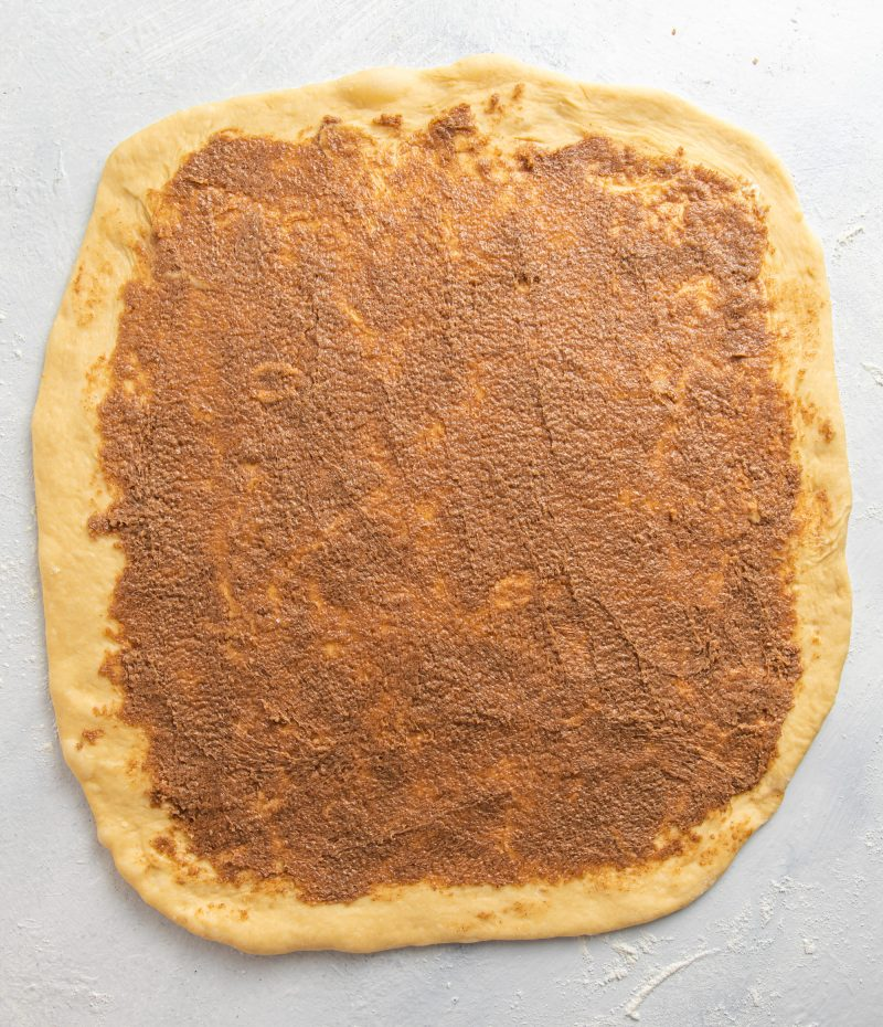 Dough rolled into a rectangular and covered with butter, sugar, cinnamon spread.