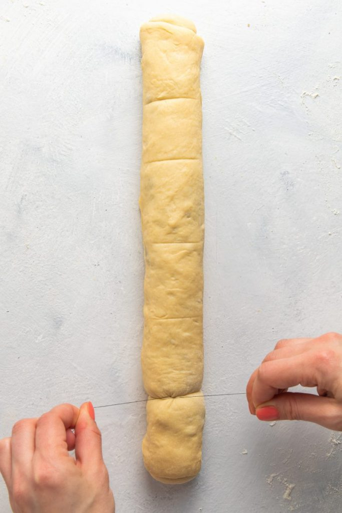 Rolled dough in the shape of a log. Two hand holding a tread on each side around the log.