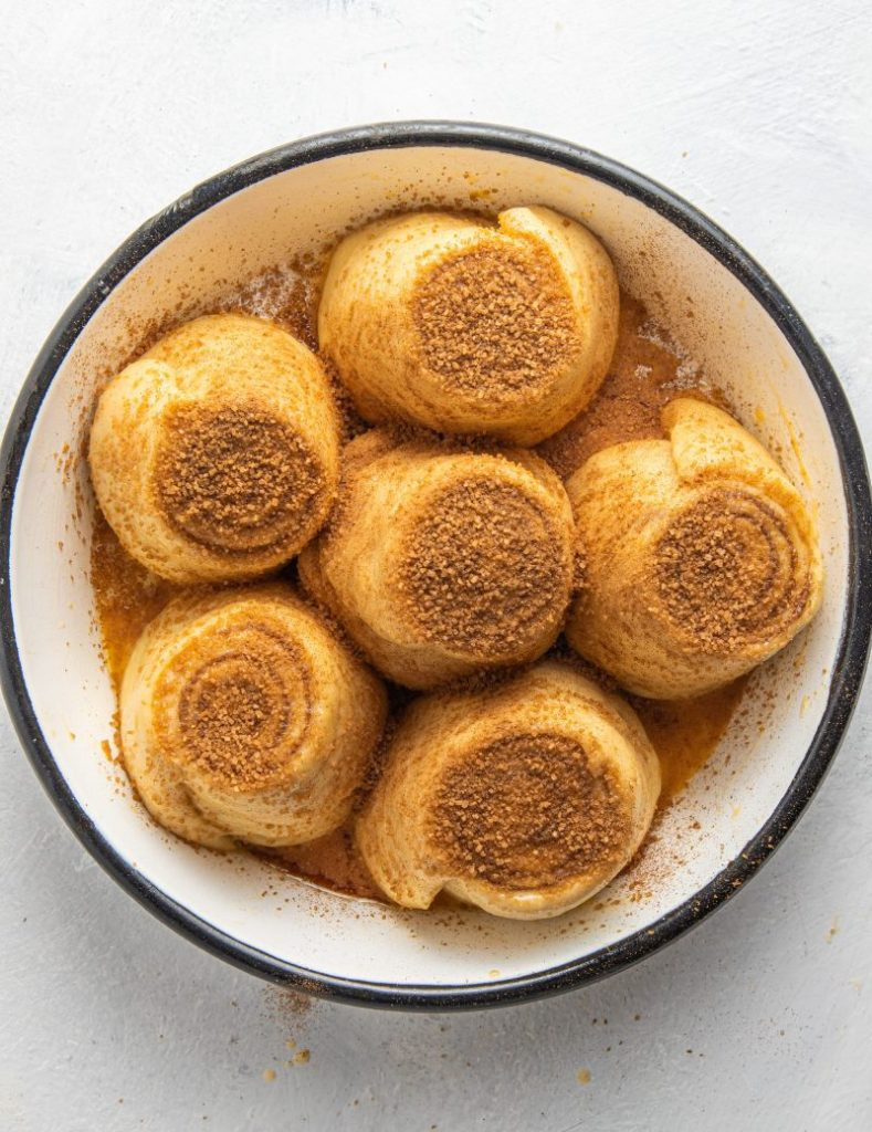 Baking dish filled with raw cinnamon rolls sprinkled with cinnamon sugar.