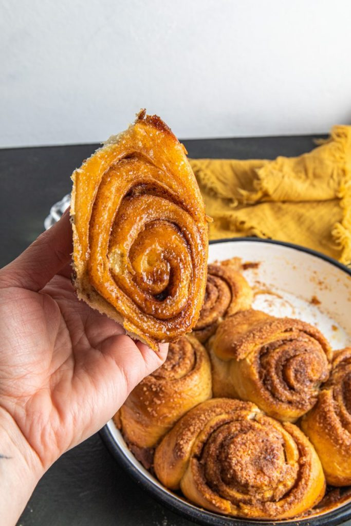 Hand holding a cinnamon roll over a baking dish filled with cinnamon rolls. Yellow napkin on the back of the dish.